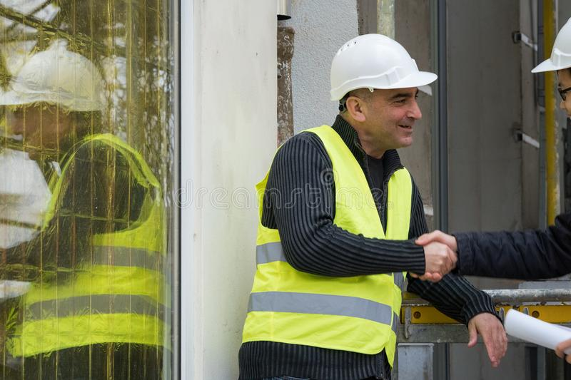 Construction worker and Asian architect shaking hands at construction site royalty free stock photography