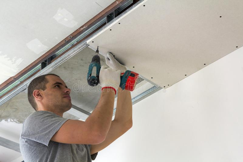Construction worker assemble a suspended ceiling with drywall an. D fixing the drywall to the ceiling metal frame with screwdriver royalty free stock photo