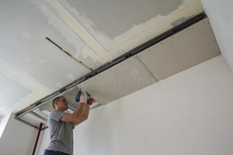 Construction worker assemble a suspended ceiling with drywall an. D fixing the drywall to the ceiling metal frame with screwdriver royalty free stock photography