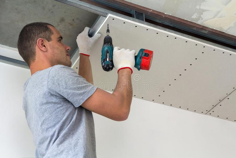 Construction worker assemble a suspended ceiling with drywall an royalty free stock photos