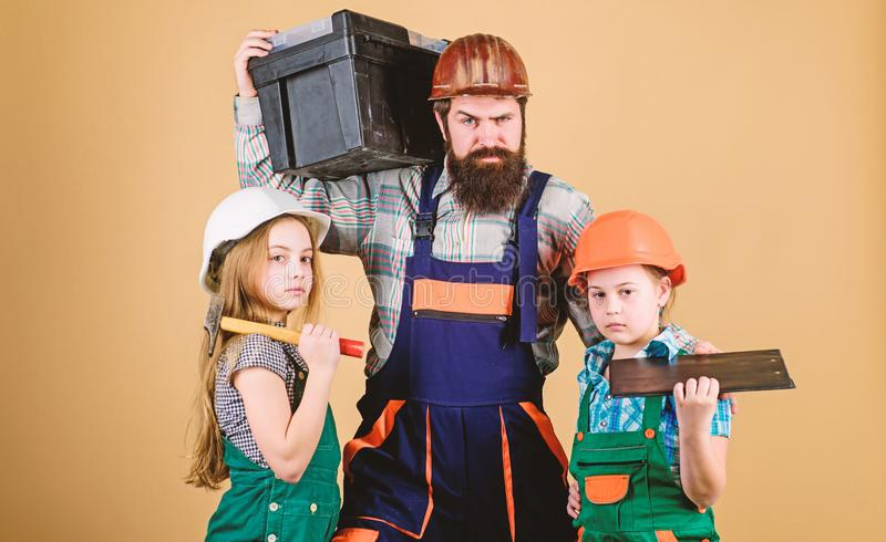 Construction worker assistant. Builder or carpenter. Repairman in uniform. Foreman. Father and daughter in workshop. Family teamwork. Repair. Bearded men with royalty free stock photo
