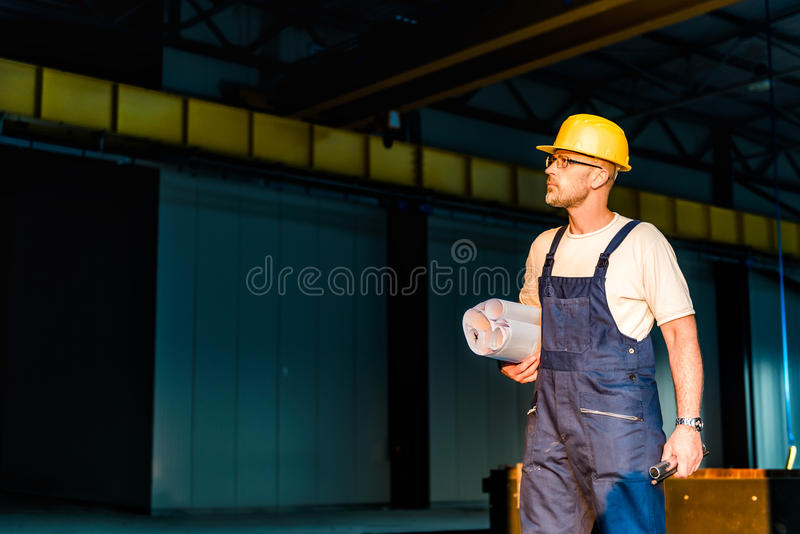 Construction worker with blue prints. Standing in big hall stock photos