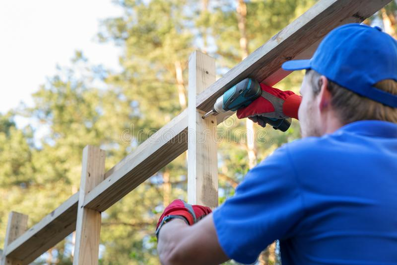 Construction worker working on wooden house structure royalty free stock photos
