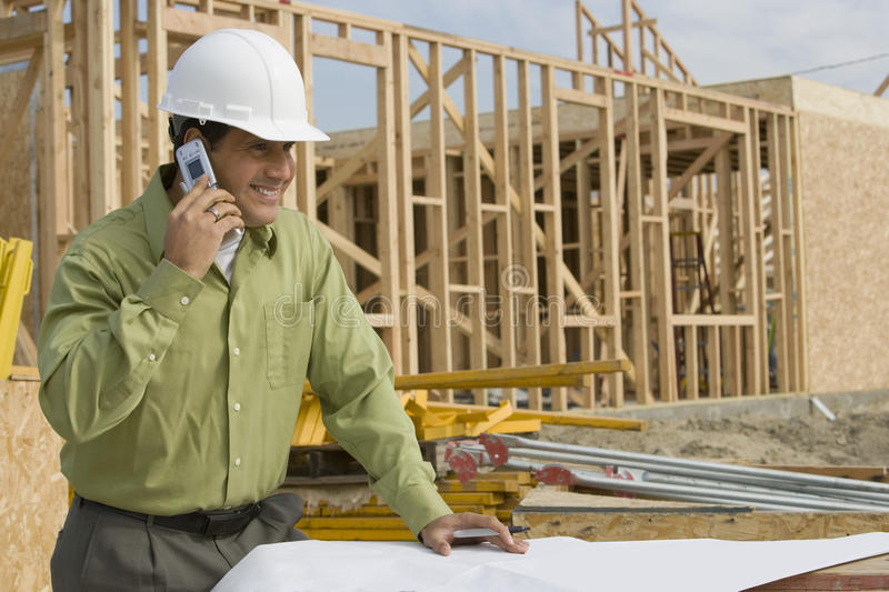 Construction Worker With Blueprints And Cellphone. Smiling construction worker with cellphone and blueprints at site royalty free stock photography