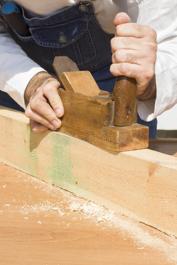 The construction worker boards the timber through a manual plane. royalty free stock photo