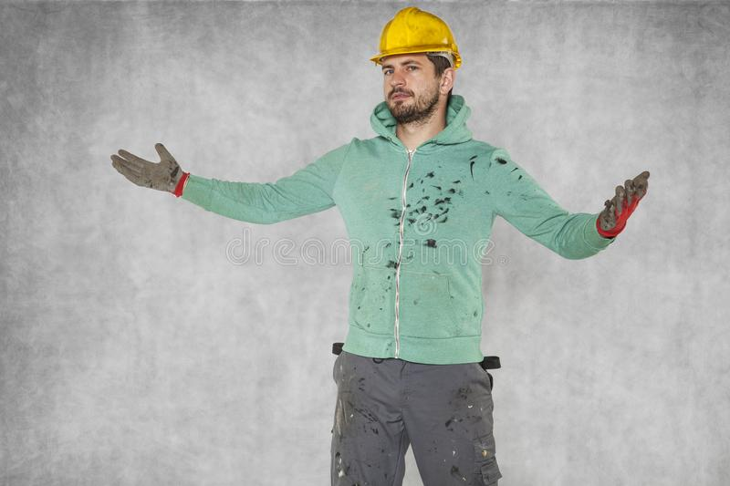 Construction worker breaks hands, gesture of powerlessness. Protective helmet on the head royalty free stock images