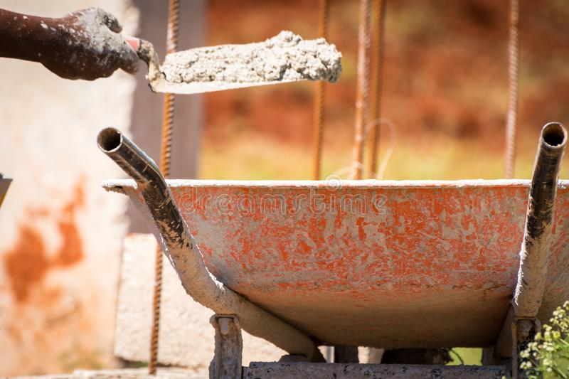 Construction worker/bricklayer/mason holding trowel with wet cement royalty free stock photos
