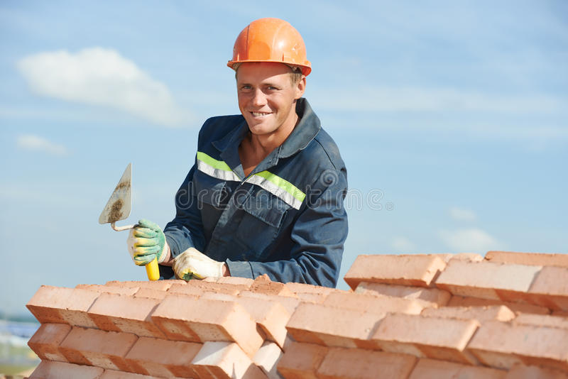 Construction worker bricklayer. Portrait of construction mason worker bricklayer with trowel putty knife outdoors at building area stock photo