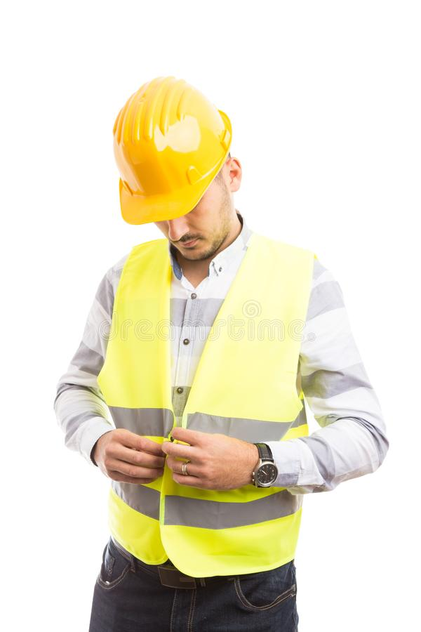 Construction worker or builder dressing for job. With green reflective vest and yellow hardhat as protection and safety equipment concept stock photography