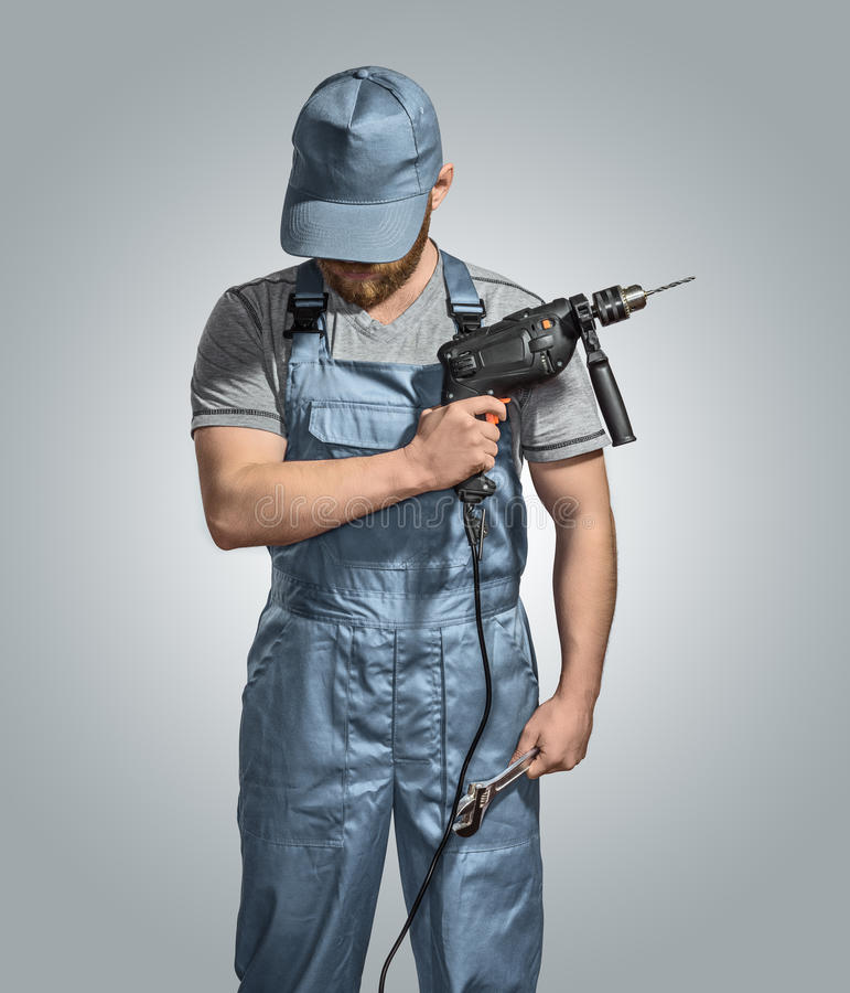 Construction worker builder with drill and wrench on the isolated background royalty free stock photos