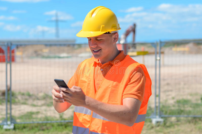 Construction worker, builder or engineer on site. Reading a text message on his mobile phone with a smile in his hardhat and high visibility clothing royalty free stock photography