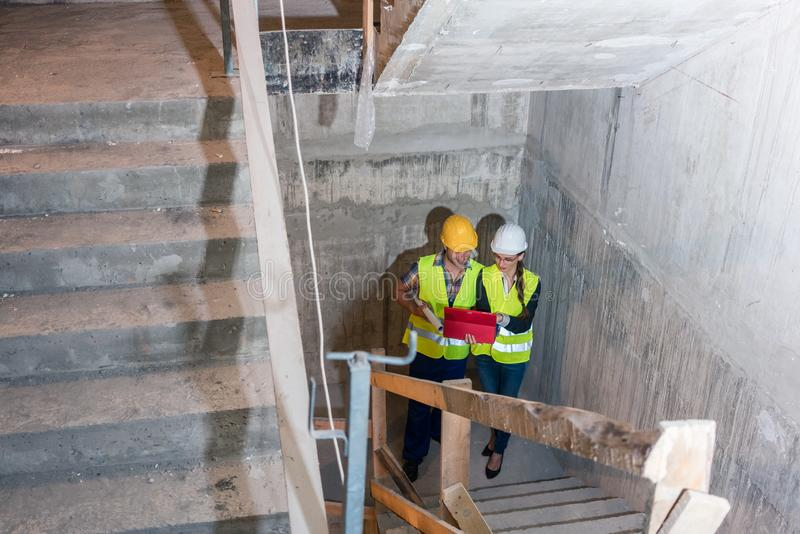 Construction worker and builder inspecting stairs in building shell royalty free stock image