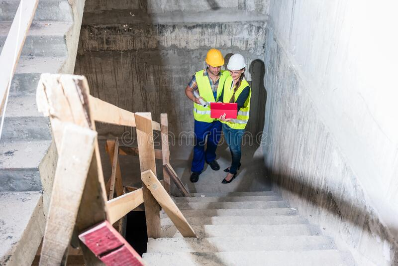 Construction worker and builder inspecting stairs in building shell stock photos