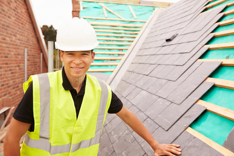 Construction Worker On Building Site Laying Slate Tiles stock photography