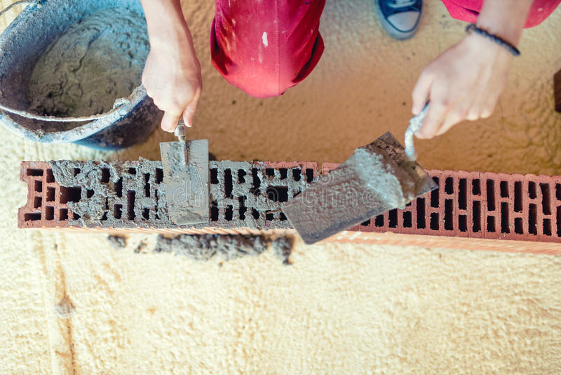 Construction worker building walls and fixing bricks with mortar and putty knife stock photo