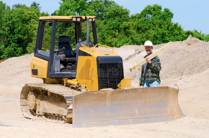 Construction worker and bulldozer. At a job site for road construction and home building royalty free stock image