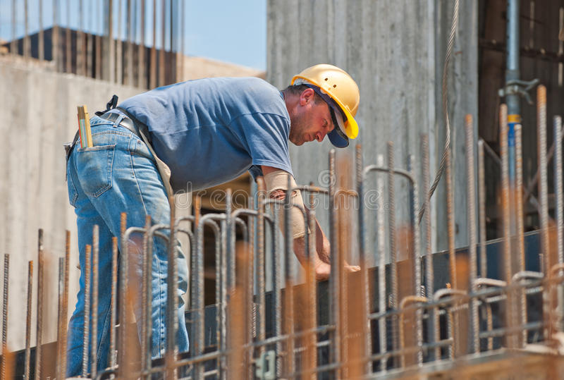 Construction worker busy with forwork frames. Authentic construction worker busy on the positioning of formwork frames in construction site royalty free stock images