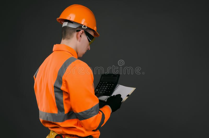 Builder. A construction worker with a calculator and a blank notebook in his hands. Cost calculation of repair or construction royalty free stock images