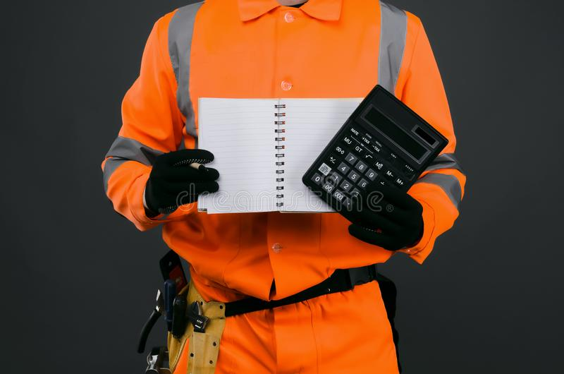 Construction invoice. A construction worker with a calculator and a blank notebook in his hands. Cost calculation of repair or construction royalty free stock images