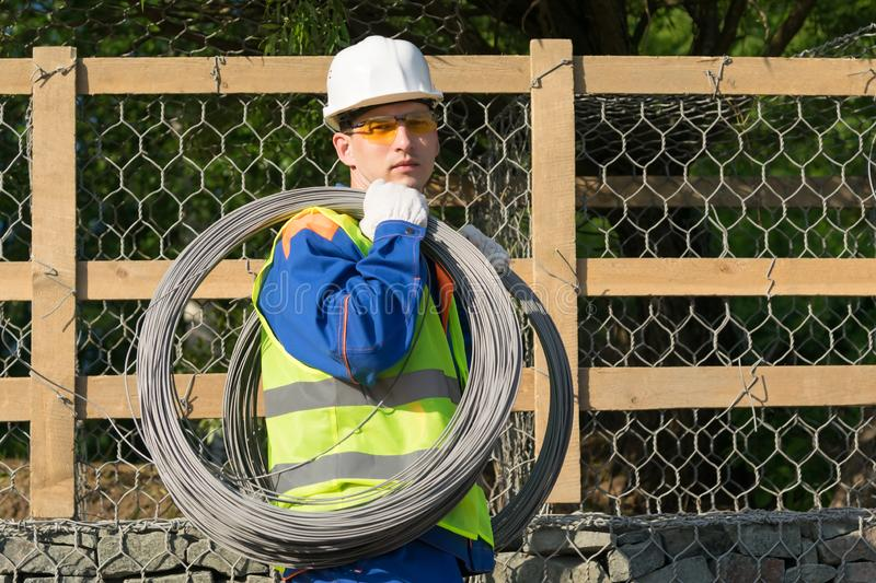 Construction worker carries a lot of steel wire on his shoulder stock image