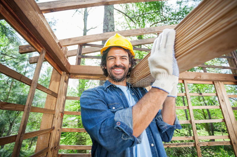 Construction Worker Carrying Wooden Planks On royalty free stock photo