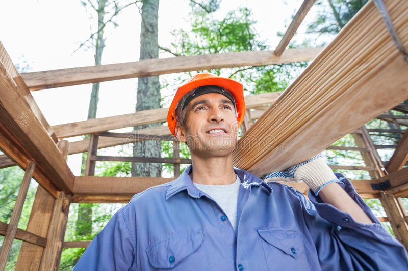 Construction Worker Carrying Wooden Planks royalty free stock photo