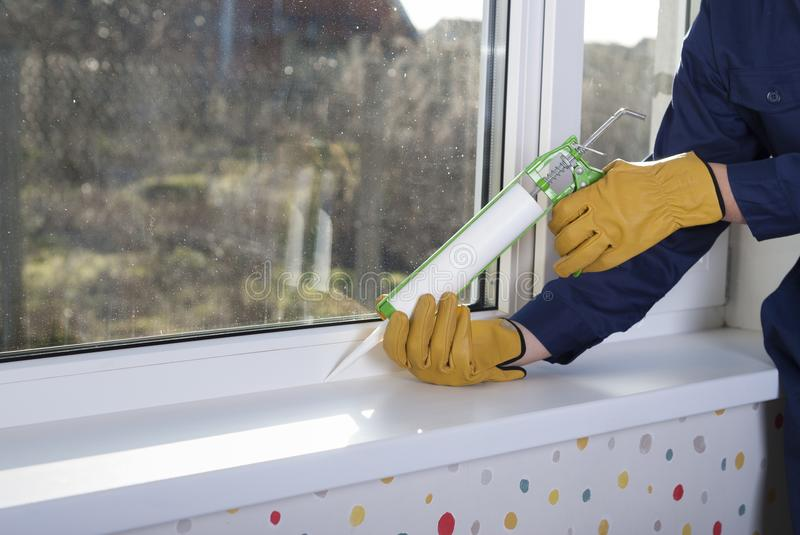 Silicone sealant and windows. Construction worker caulking window frame with silicone sealant royalty free stock photo