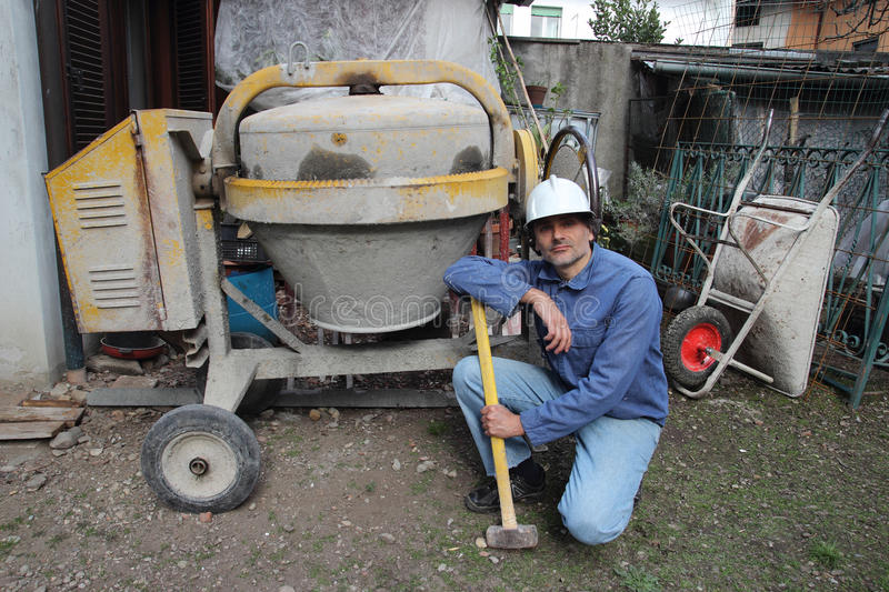 Construction worker with cement mixer. Construction Worker with Mixing Cement machine stock photos