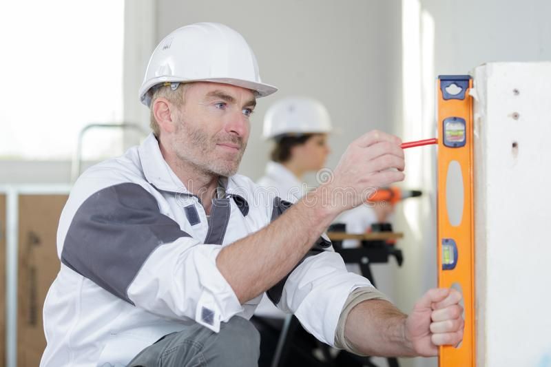 Construction worker check level on wall stock image