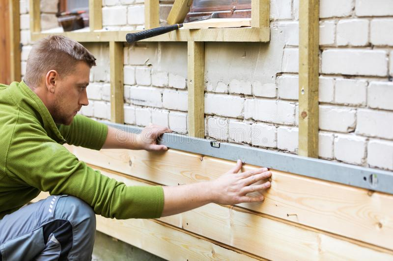 Construction worker checking level of house wood facade royalty free stock photo