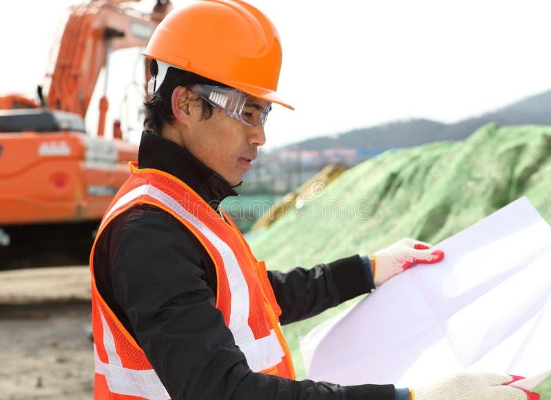 Construction worker checking blueprint stock photos