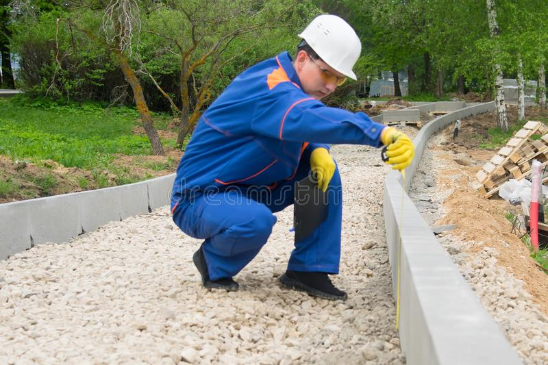 Construction worker checks the progress of laying curbstone and rubble mound royalty free stock photography