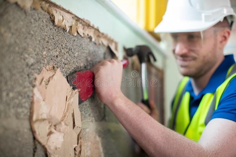 Construction Worker With Chisel Removing Plaster From Wall In Renovated House stock image