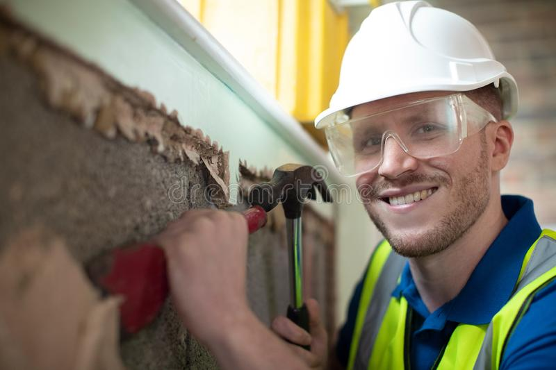 Portrait Of Construction Worker With Chisel Removing Plaster From Wall In Renovated House stock images