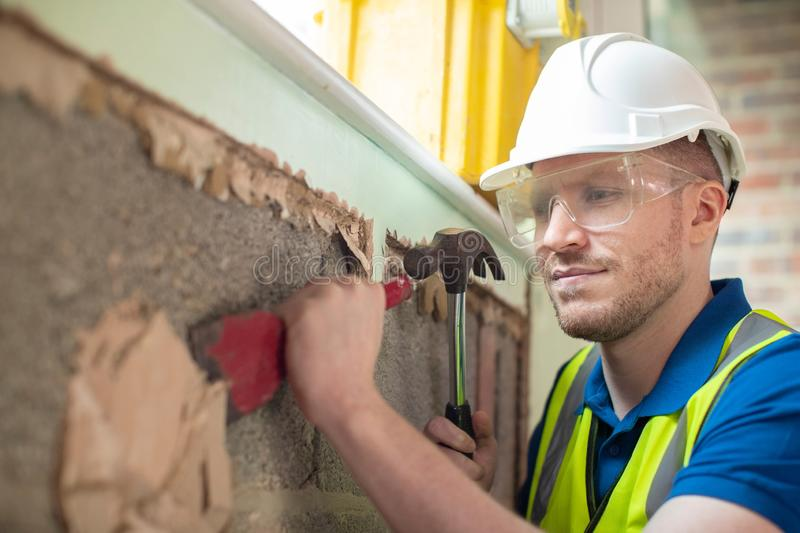 Construction Worker With Chisel Removing Plaster From Wall In Renovated House royalty free stock photography
