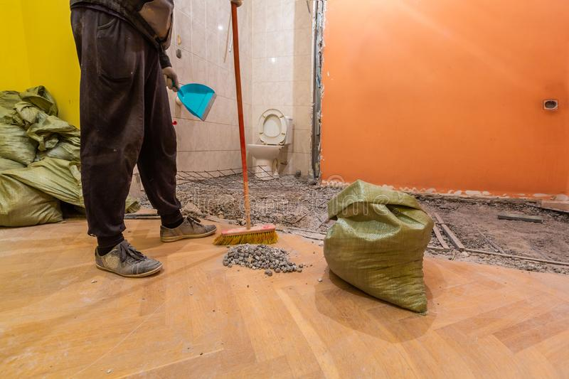 Construction worker is cleaning construction trash in the bags in the toilet room or restroom in apartment that is unde royalty free stock images