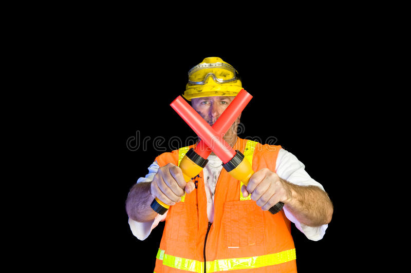 Construction worker with communication flashlights. A construction worker uses flashlight signaling devices to communicate activity stock photos