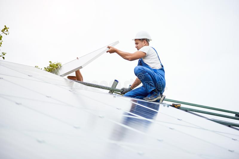 Installing of solar photo voltaic panel system. Construction worker connects photo voltaic panel to solar system using screwdriver. Professional installing and royalty free stock photo