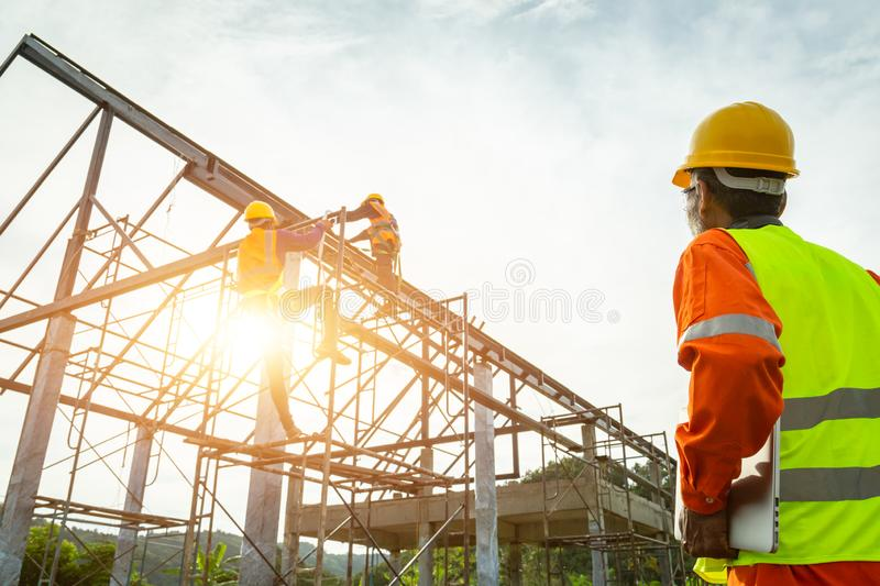 A construction worker control in the construction of roof structures on construction site and sunset background stock images