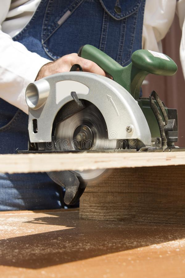 The carpenter cuts the board with a manual electric saw. stock image