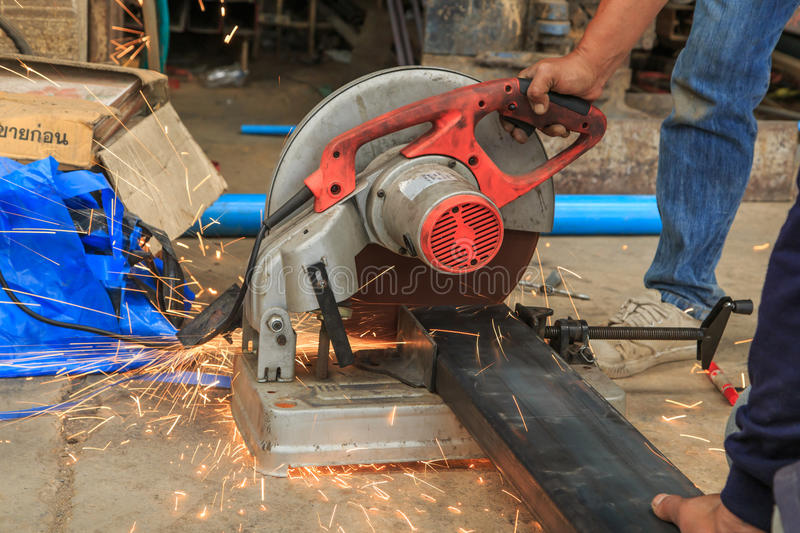 Construction worker cuts hollow steel square tube with circular saw royalty free stock photos