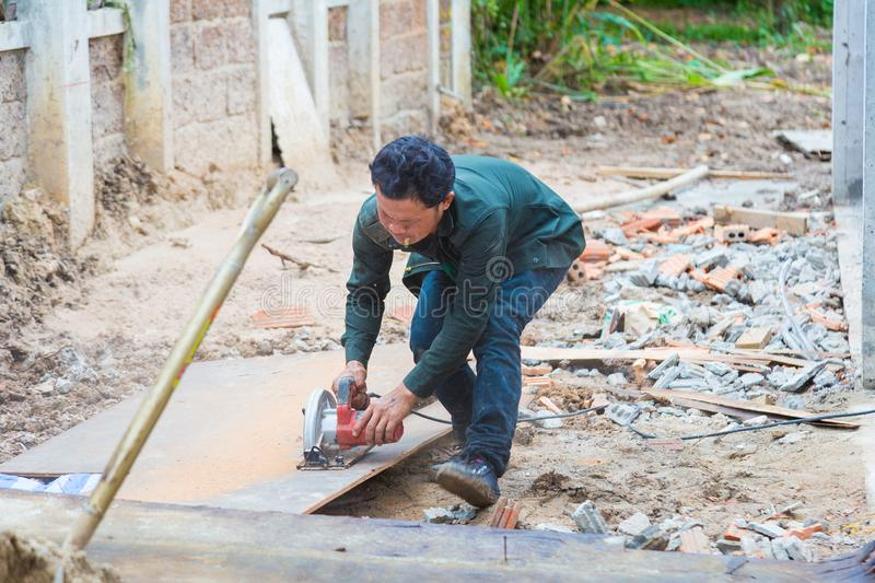 Construction worker cuts construction plywood at a construction royalty free stock photo