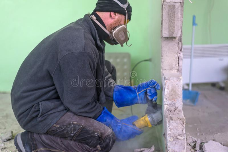 Construction worker cutting concrete wall by using electric cutter stock images