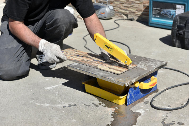 Construction worker. Cutting the facing tile royalty free stock image