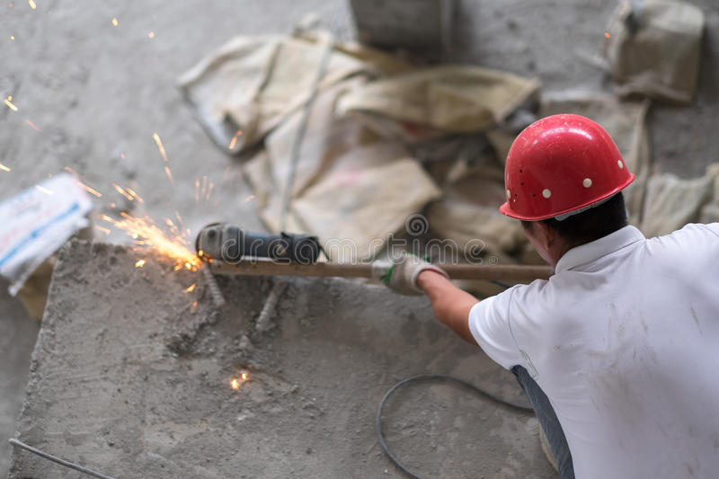 Construction Worker Cutting Metal Rebar. An asian construction worker is cutting metal rebar while squatting on a concrete pillar. He is wearing a red hard hat royalty free stock image