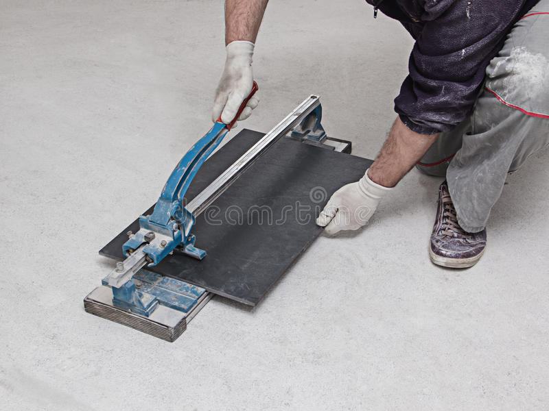 Construction worker is cutting tiles at home stock photos