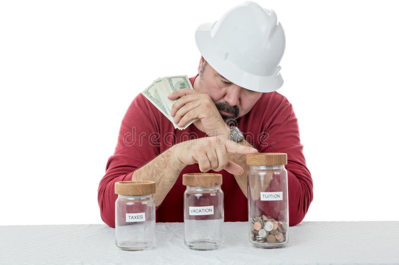 Construction worker decides over the use of money. Construction worker wearing a hardhat deciding over the use of money between, taxes, vacations or tuitions royalty free stock photos