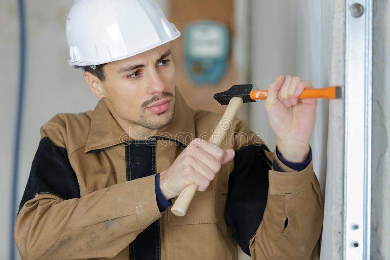 Construction worker demolishing old brick wall with chisel tool. Male royalty free stock photos