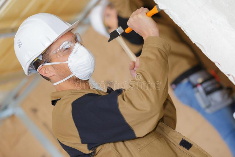 Construction worker demolishing old wall with chisel and hammer. Indoors stock photography