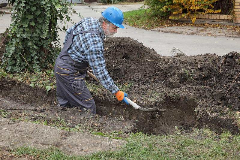 Construction worker digging trench using shovel royalty free stock image